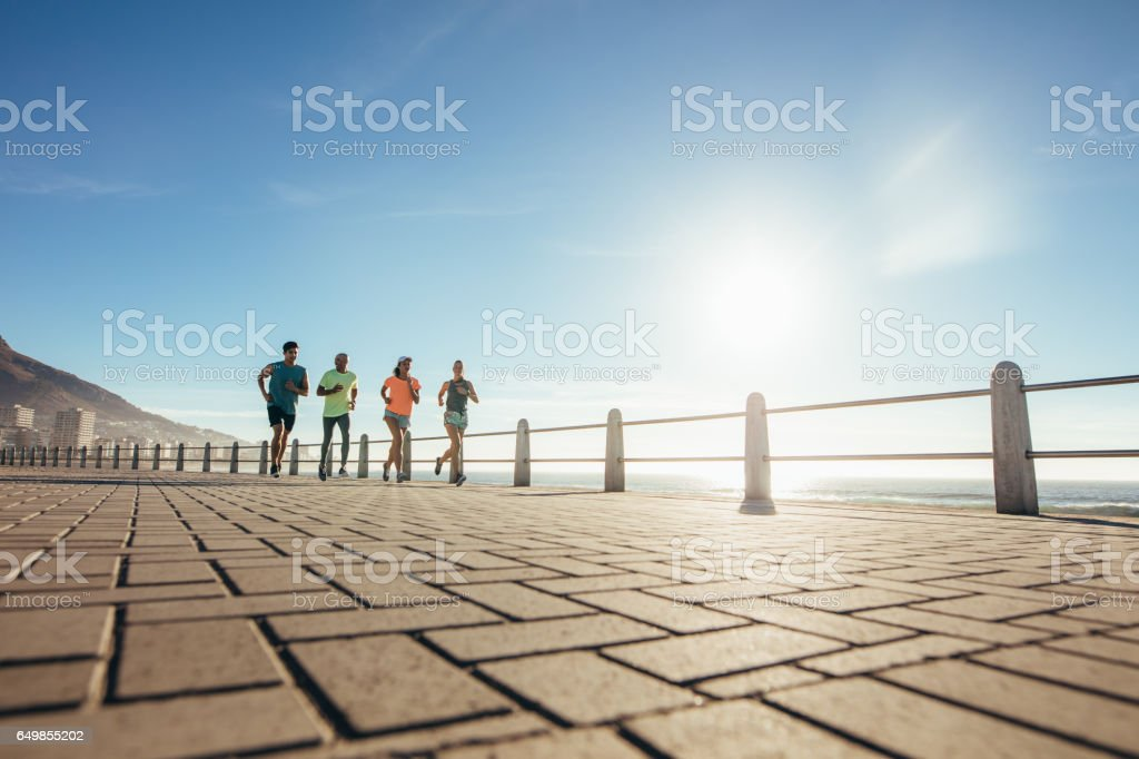 Young people running on ocean water front stock photo