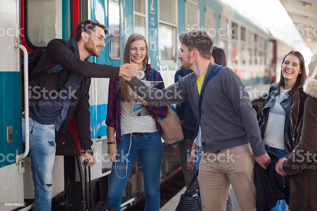 Young people saying goodby on a train station stock photo