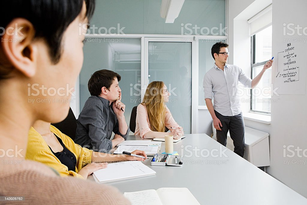 Young People Sitting At Conference Table Man Explaining Chart Stock - 20 person conference table