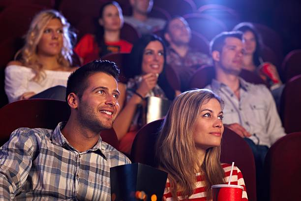 Young people sitting at movie theater stock photo