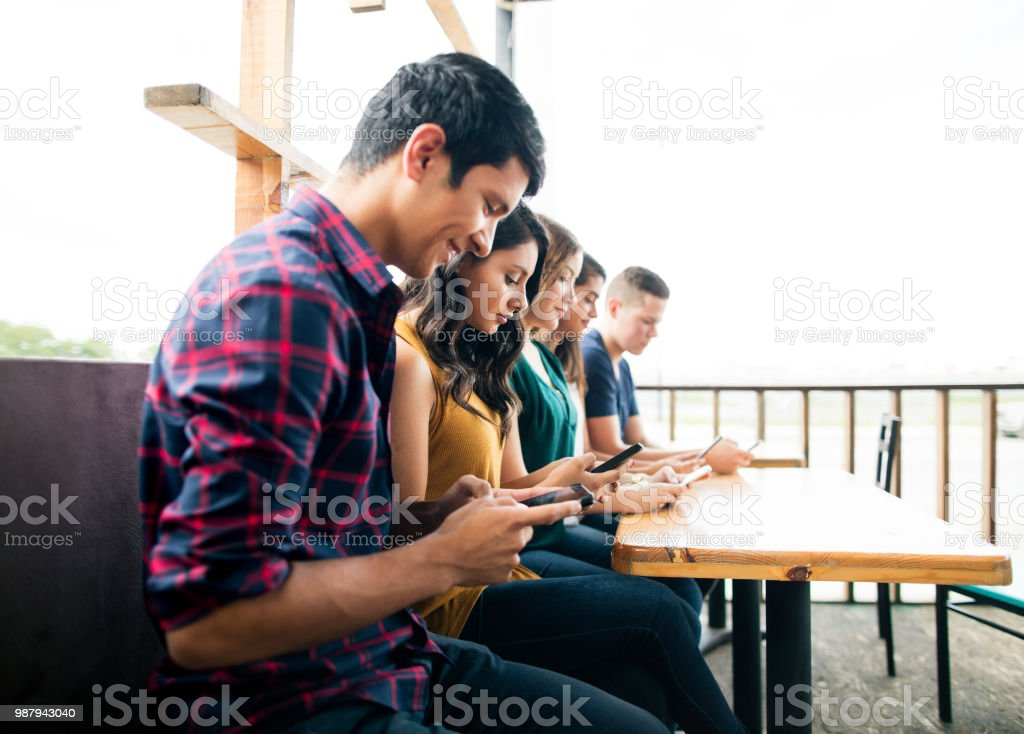Young people sitting at table and using mobile stock photo