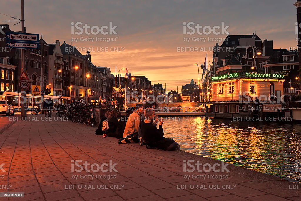 Young people sitting canal at night stock photo