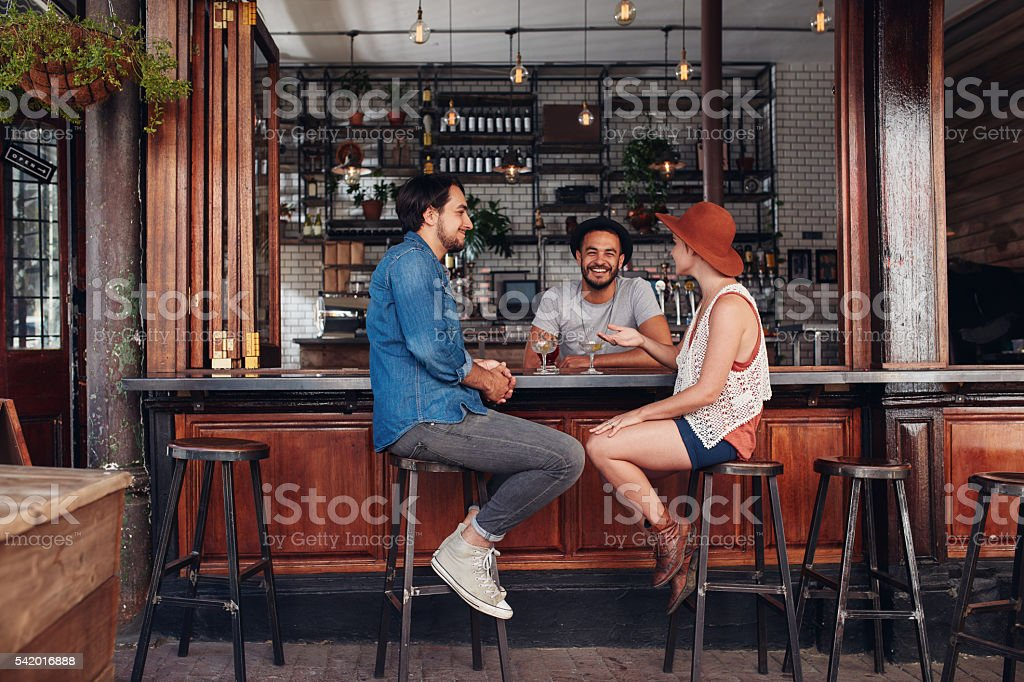Young people sitting in a cafe and talking stock photo