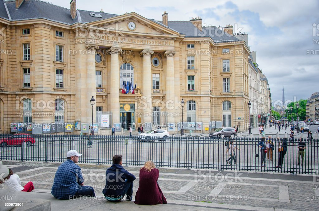 Young people sitting in front of Mairie du 5e arrondissement stock photo