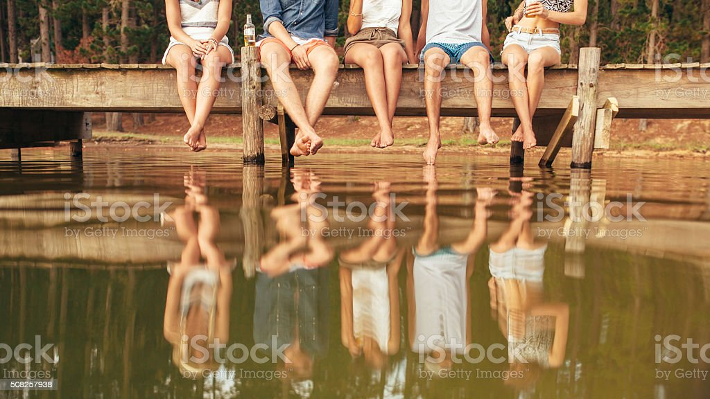 Young people sitting on the edge of a pier stock photo