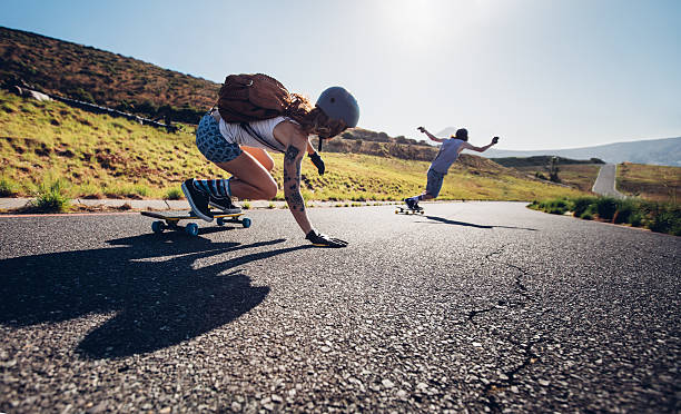 Young people skateboarding outdoors on the road stock photo