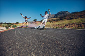 Young people skateboarding with smoke bomb on the road. Young man and woman practicing skating on a rural road.
