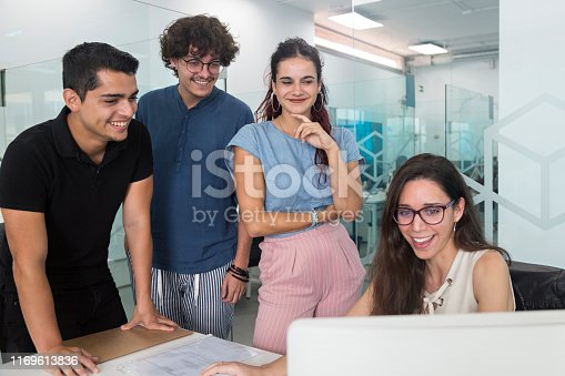 istock Young people smiling and surprised watching a computer in a coworking office. 1169613836