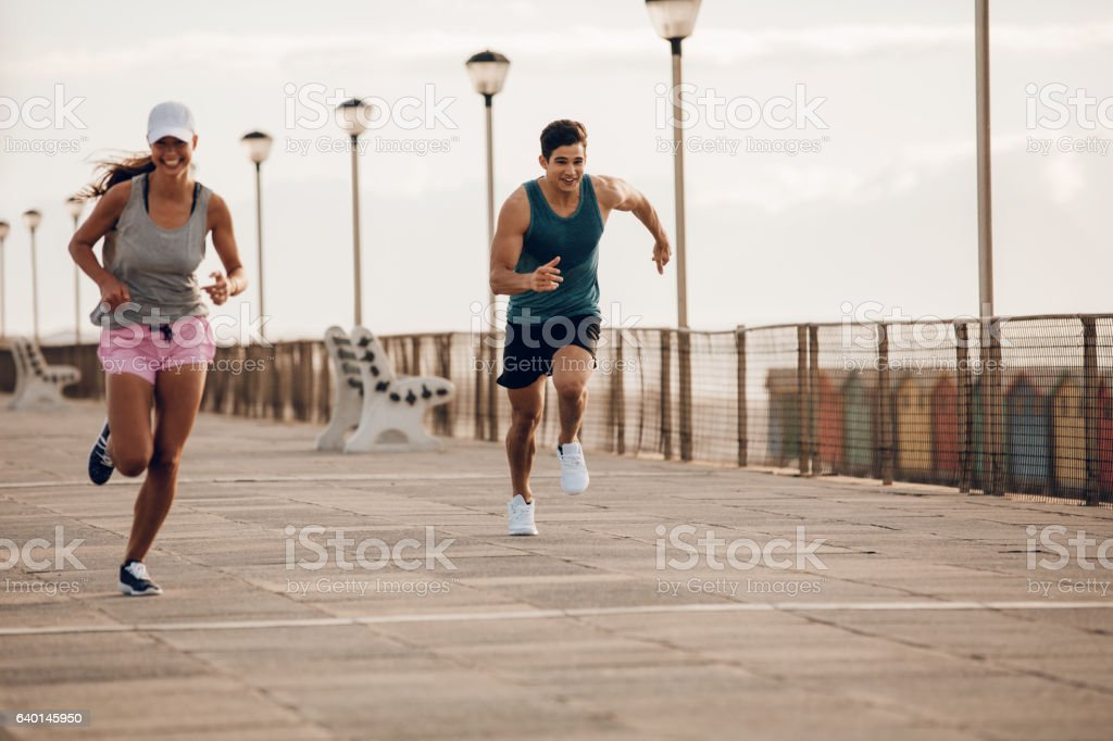 Young people sprinting along a seaside promenade stock photo