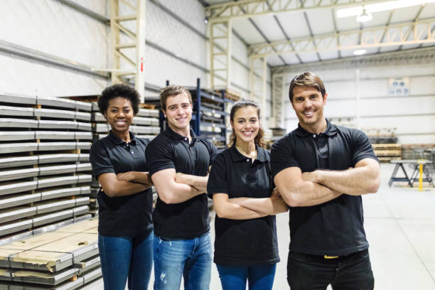 young people standing together in factory - uniform stock photos and pictures