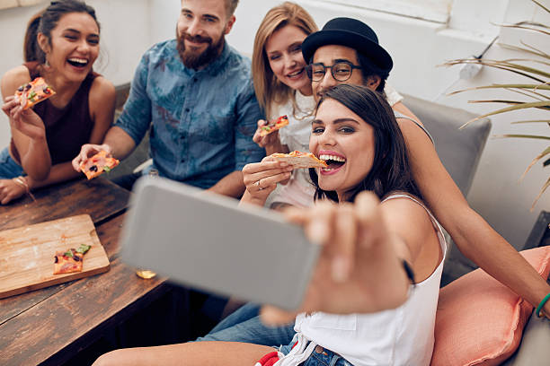 young people taking a selfie while eating pizza - eating technology stock photos and pictures