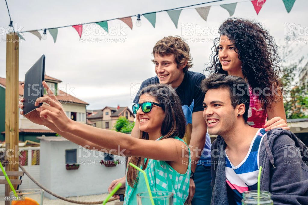 Young people taking a selfie with tablet in party royalty-free stock photo