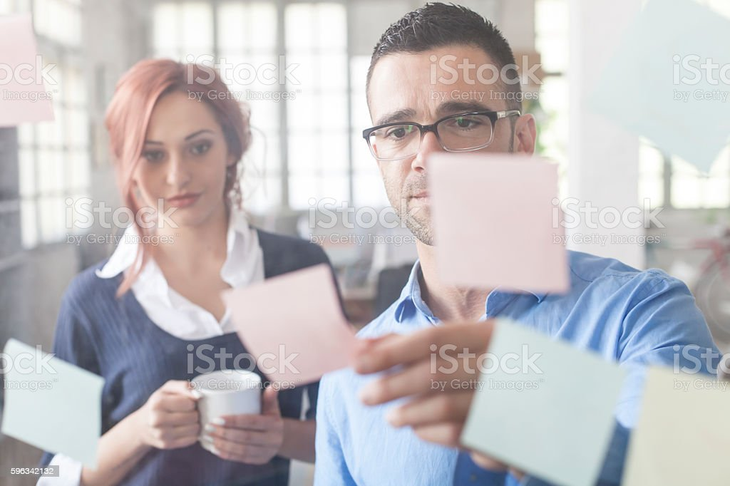 Young people taking reminders from glass wall royalty-free stock photo