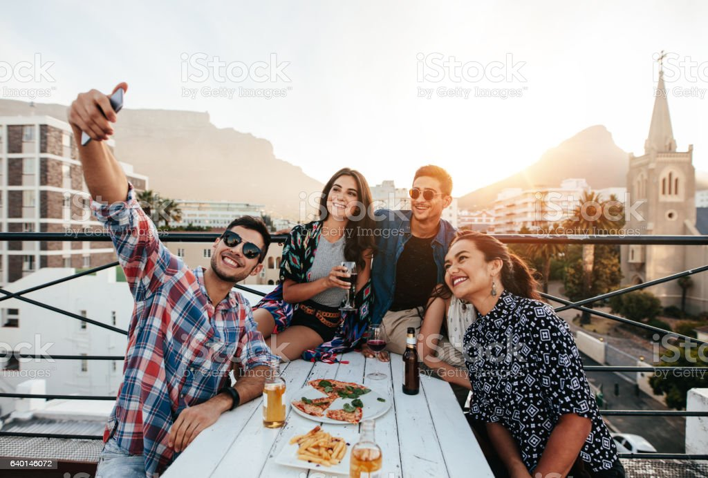 Young people taking selfie on rooftop party stock photo