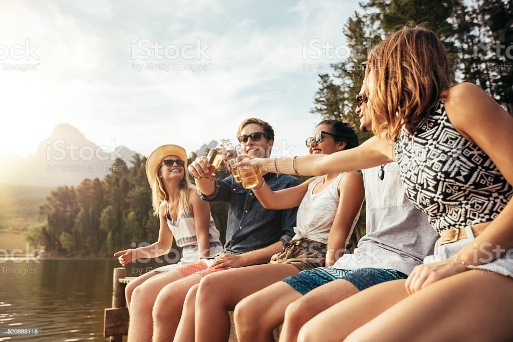 Young people toasting beers on a jetty stock photo