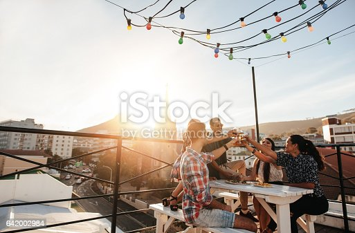 istock Young people toasting drinks at party 642002984