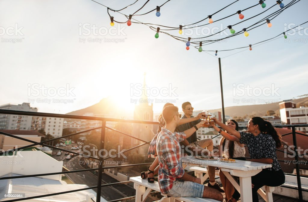 Young people toasting drinks at party stock photo