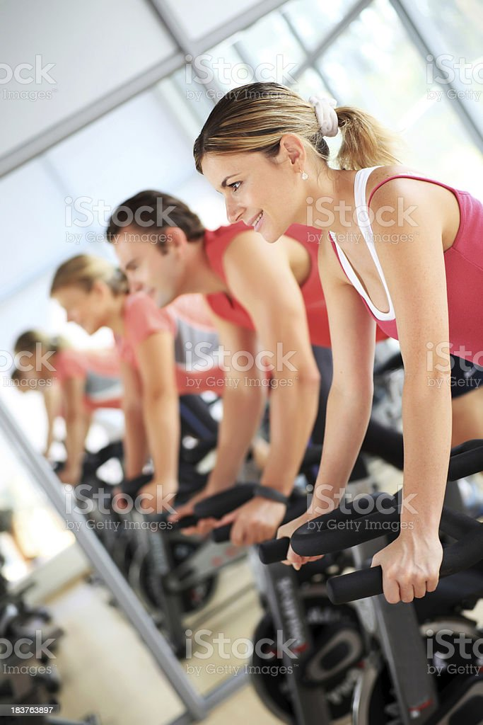 Young people training on exercise bike at the gym royalty-free stock photo