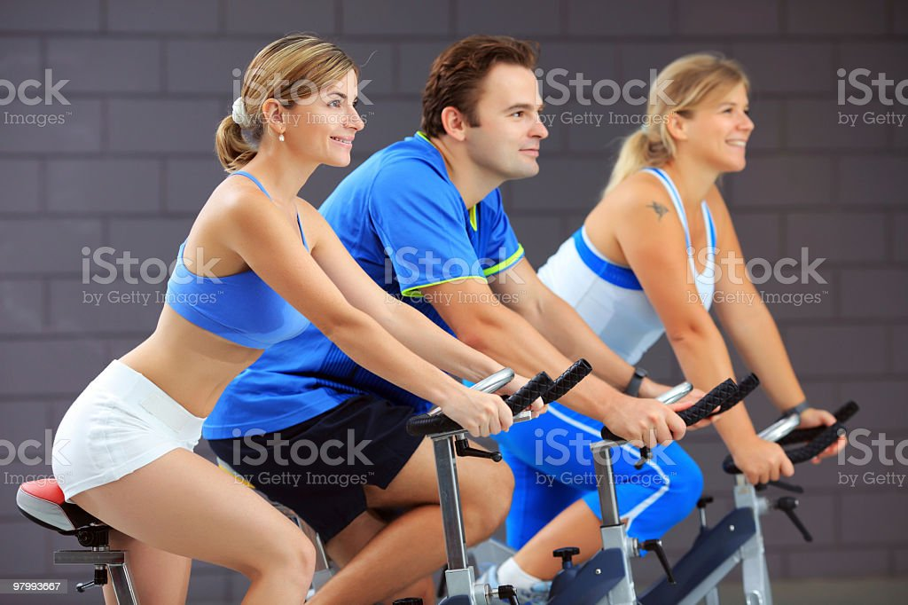 Young people training on exercise bike at the gym. royalty free stockfoto