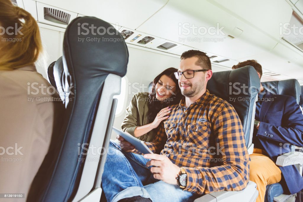 Young people traveling by airplane using digital tablet stock photo