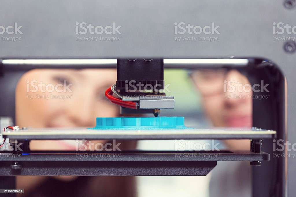 Young people using 3D printer Close up of 3D printout. Young people faces in the background. 3D Printing Stock Photo