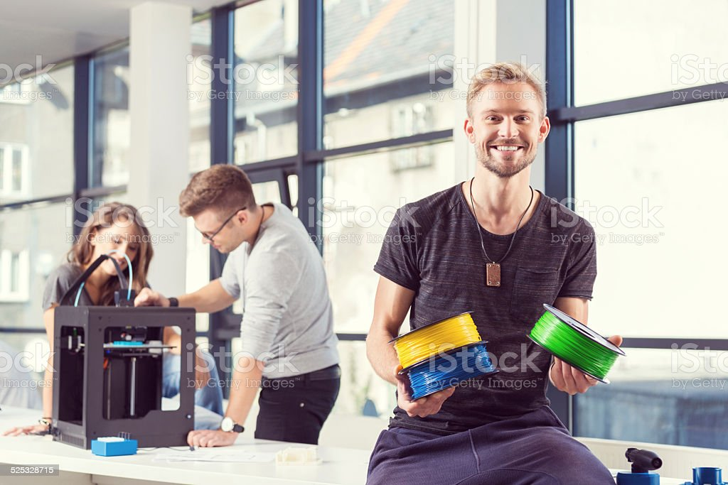 Young people using 3D printer Start-up business team using a 3D printer. Young man holding filaments and smiling at the camera. 3D Printing Stock Photo