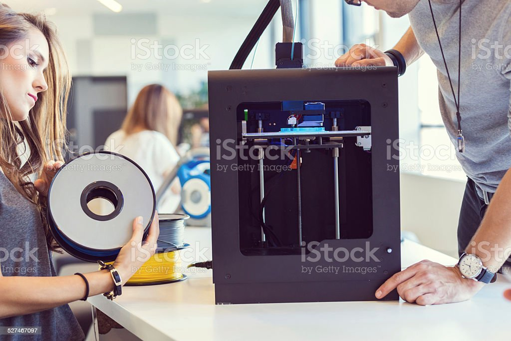 Young people using 3D printer Start-up business team working together in the office, close up of couple using a 3D printer.  3D Printing Stock Photo