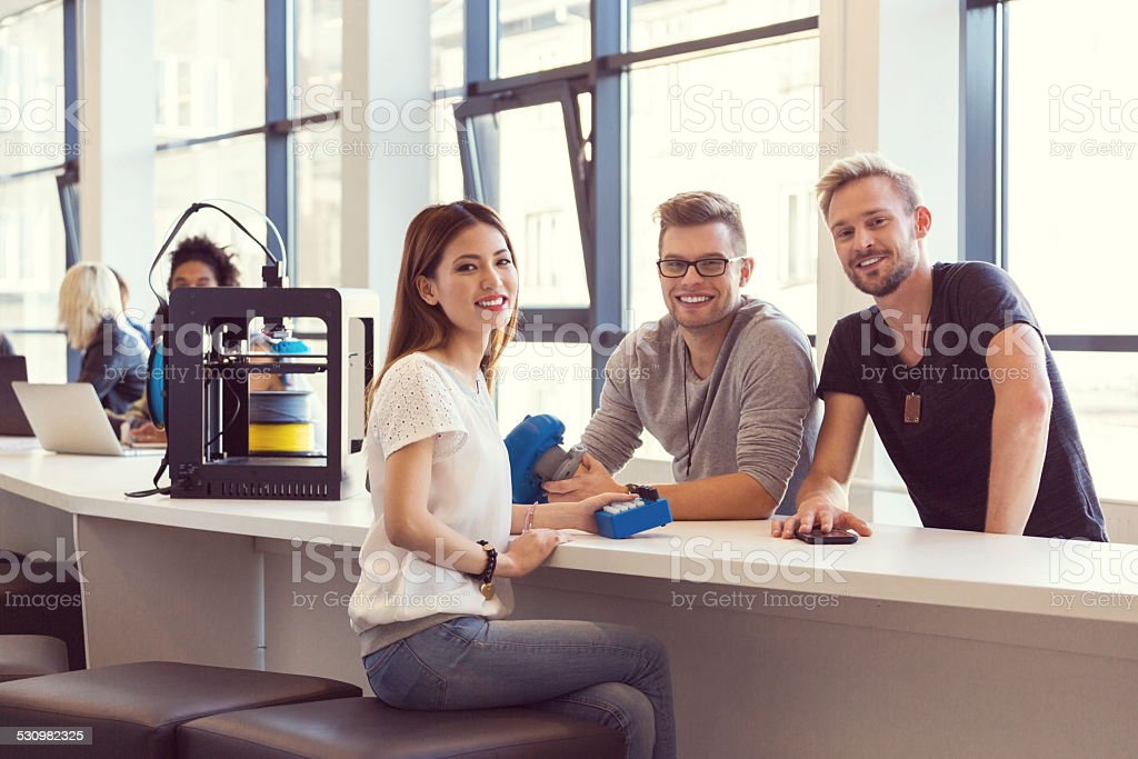 Young people using 3D printer Start-up Business. Three young people sitting a the table, holding 3D printouts in hands and smiling at camera. 3D printer next to them. 2015 Stock Photo
