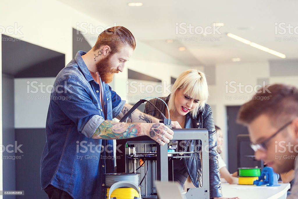 Young people using a 3D printer Bearded man with tatoos using a 3D printer in an office with his coworker. 2015 Stock Photo