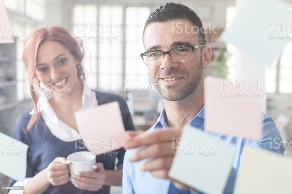 Young people using adhesive notes stock photo