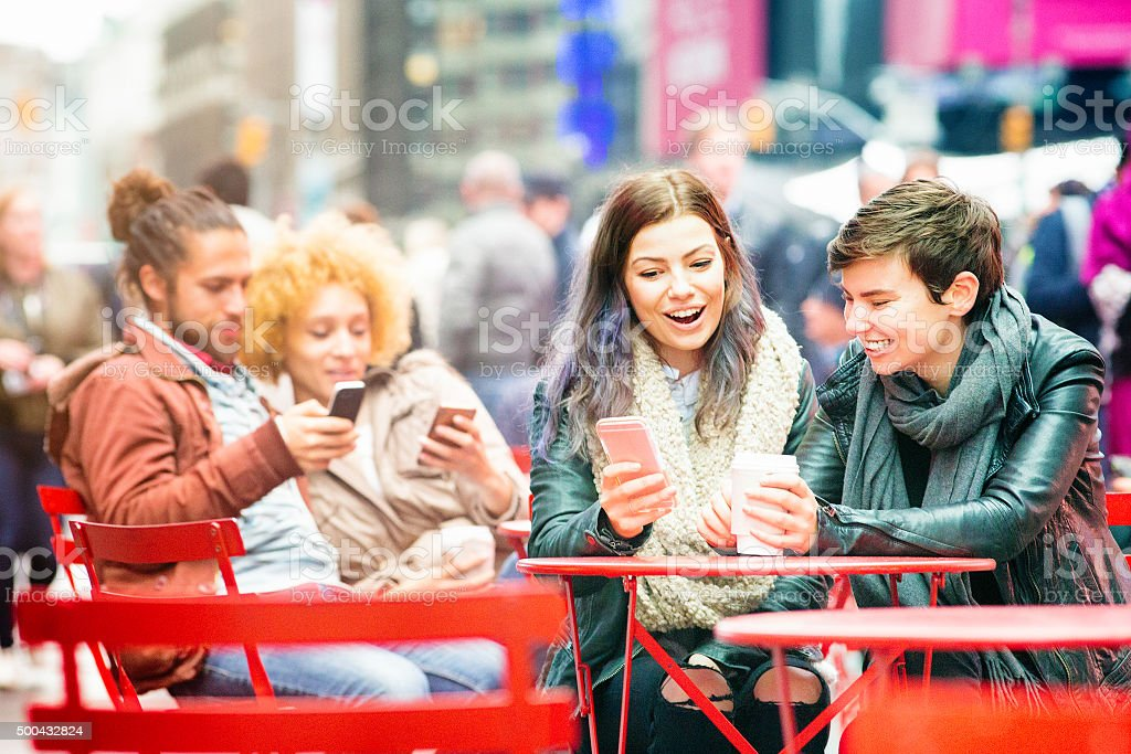 Young people using phones sitting in Times Square stock photo