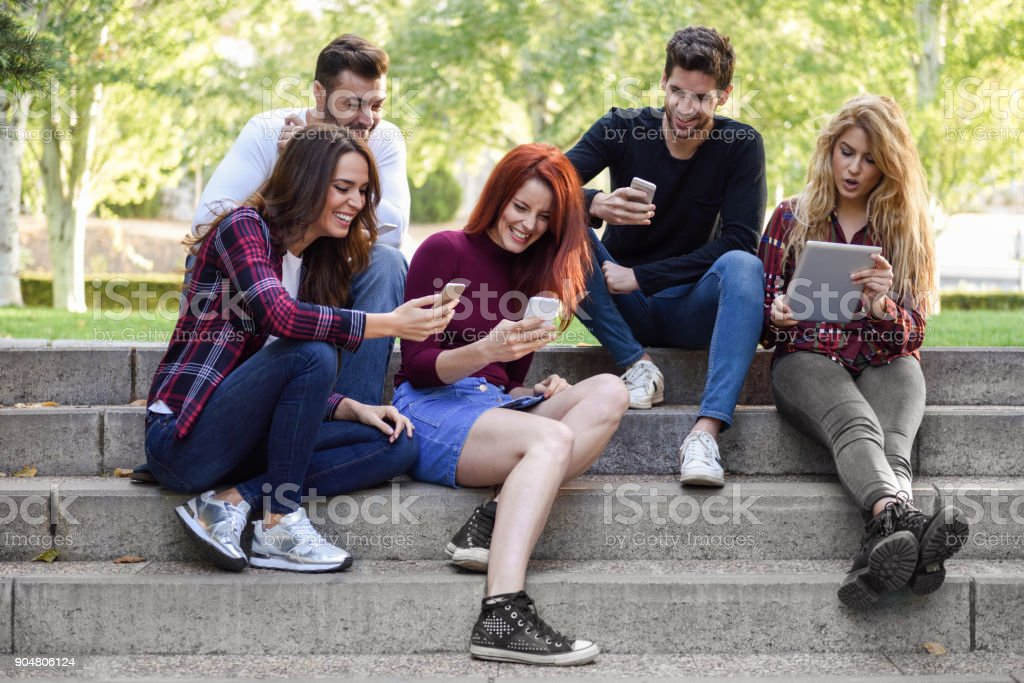 Young people using smartphone and tablet computers outdoors stock photo