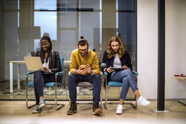 Young people using technology in waiting room Students relaxing between lessons, using different devices to surf the internet in waiting room, at University man bun stock pictures, royalty-free photos & images
