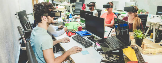 Young people using virtual reality glasses in coworking office - Teamwork creating new digital contents - Technology trends, social media network, marketing and concept - Focus on bottom man headset stock photo
