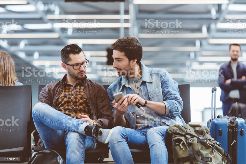 Young people waiting for flight using mobile phone stock photo