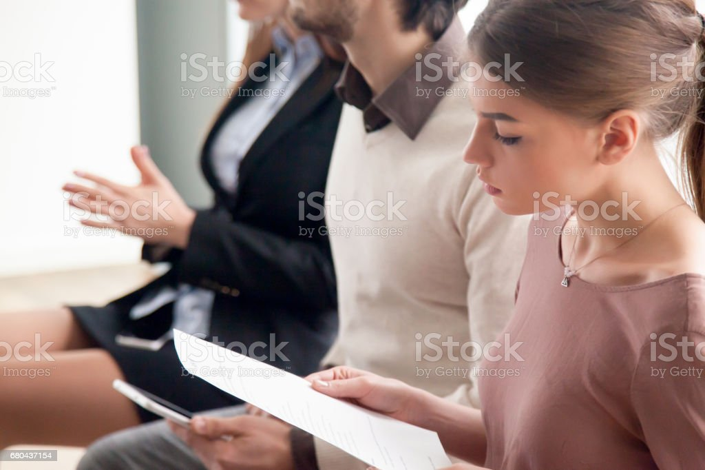 Young people waiting for job interview, audition or training indoors stock photo