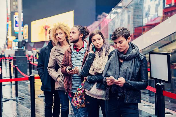 giovani in attesa in linea per acquistare biglietti aerei per new york. - queue foto e immagini stock