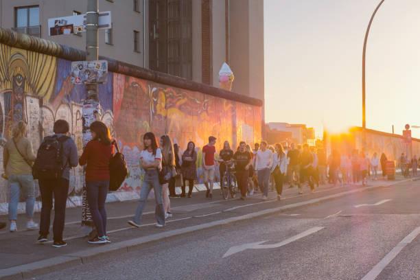 junge menschen zu fuß in der berliner mauer (east side gallery) auf sommer tag abend mit sonnenuntergang himmel - kreuzberg stock-fotos und bilder