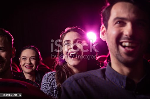 Group of happy people watching funny movie in the cinema. Close up of faces.