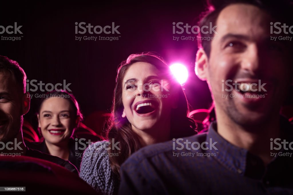 Young people watching comedy movie in the cinema stock photo