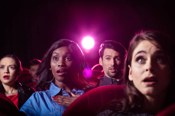 Young people watching thriller movie in the cinema Multi ethnic group of young people watching scary movie in the cinema. gasping stock pictures, royalty-free photos & images