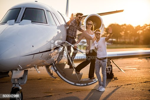 Three people standing on the stairs of private jet airplane and waving. They are all wearing sunglasses. Bright sunlight is in the background.