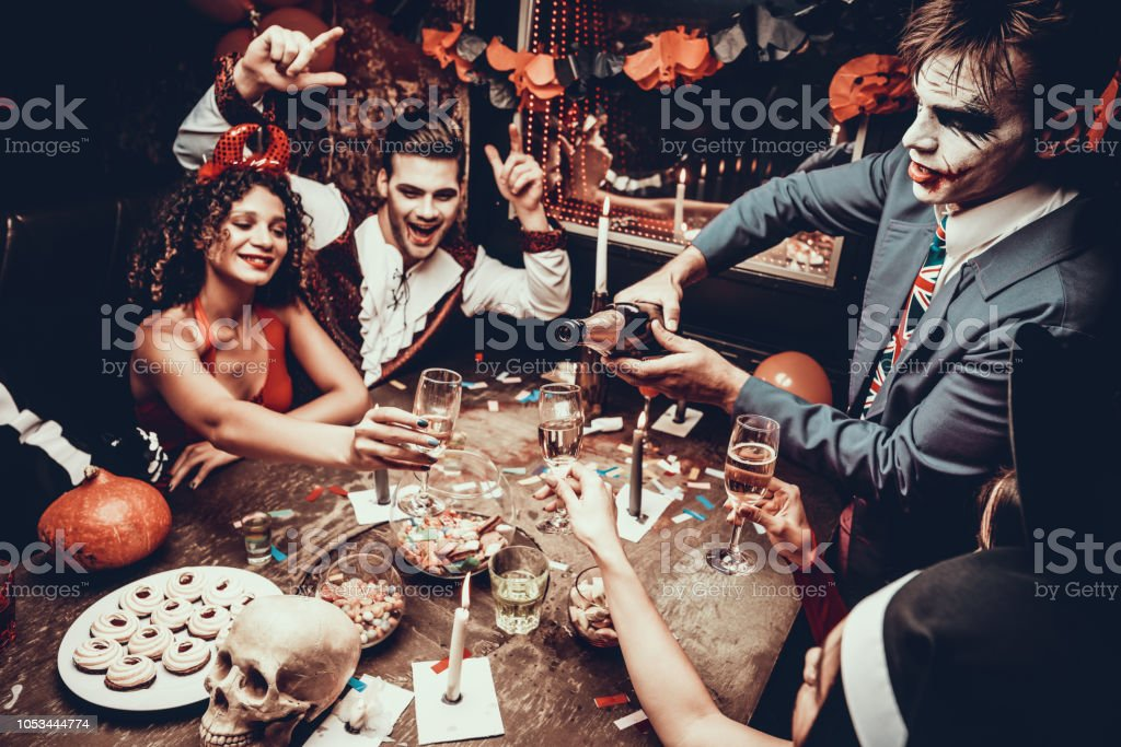 Young People Wearing Costumes Drinking Champagne Young People Wearing Costumes Drinking Champagne. Group of Young Happy People in Costumes at Halloween Party Sitting at Table and Drinking Champagne. Young Man Pouring Champagne Adult Stock Photo