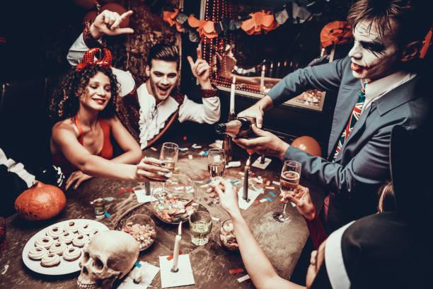 jugendliche tragen kostüme champagner trinken - halloween party lebensmittel stock-fotos und bilder