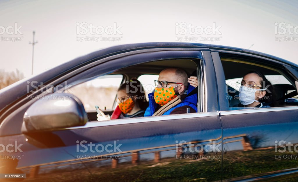 COVID-19, Young people wearing disposable face mask while driving 30-34 Years, Adult, Adults Only, COVID-19 30-34 Years Stock Photo