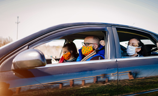 Covid19 Young People Wearing Disposable Face Mask While Driving Stock Photo - Download Image Now