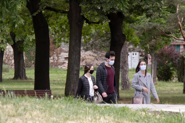 Young people wearing face masks while walking in nature, in city public park