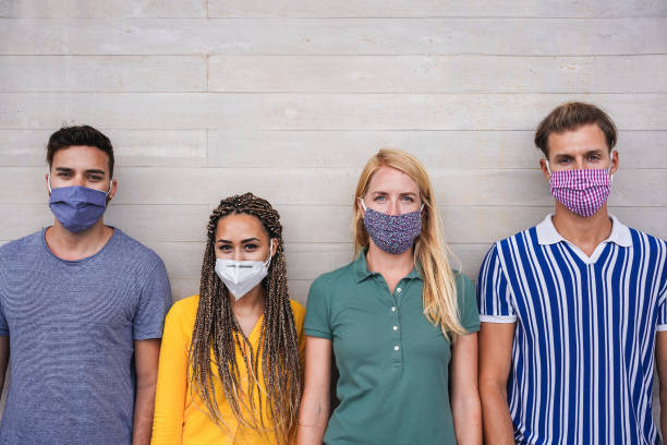 Young people wearing face protective masks for coronavirus prevention - Covid 19 lifestyle and millennial generation concept - Main focus on center faces stock photo