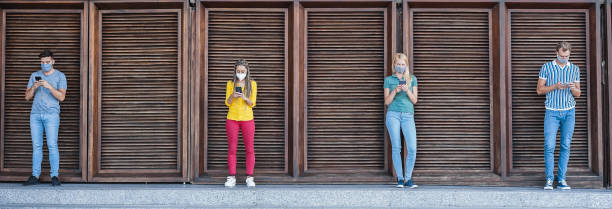 Young people wearing face safety masks using smart mobile phones while keeping social distance during coronavirus time - Technology and covid-19 spread prevention concept - Main focus on center girls stock photo