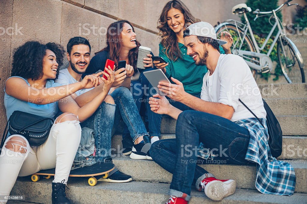 Young people with communication devices stock photo